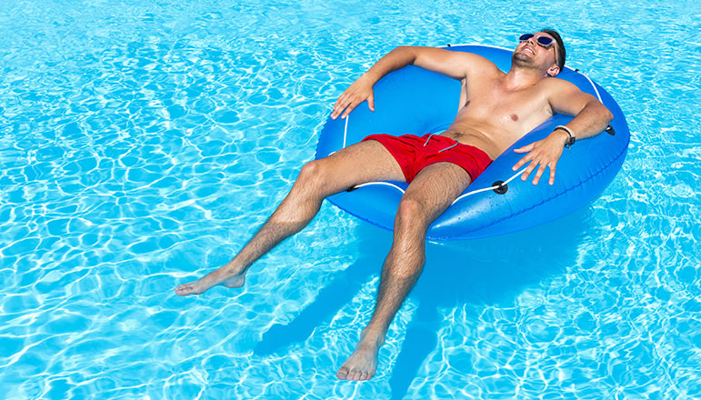 man relaxing in a pool on a raft