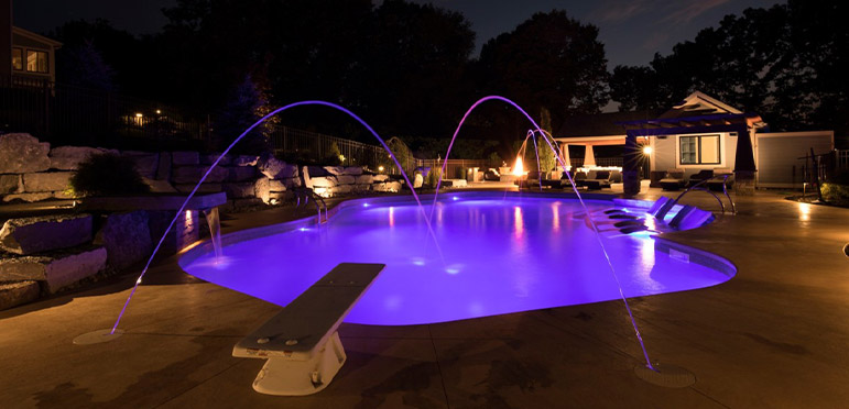 Pool and water features illuminated with purple LED lights